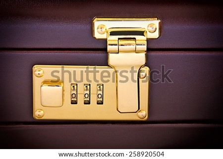 Close-up of suitcase's golden code lock.