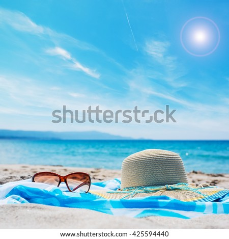 close up of sunglasses and straw hat on the beach - stock photo