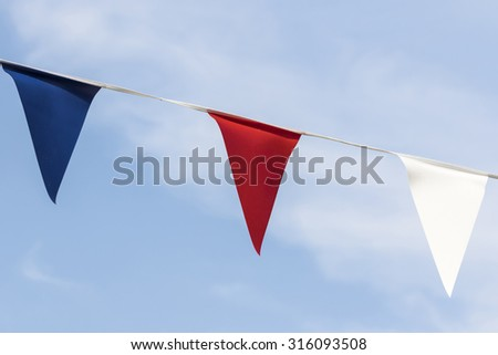 Close up of sunlit red white and blue triangular bunting against a blue sky - stock photo