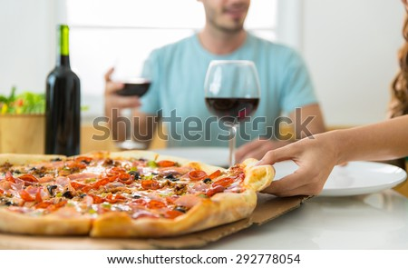 Close up of supreme pizza slice and people eating and enjoying wine at home delivery - stock photo