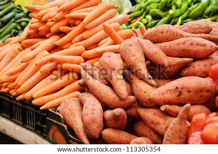 close up of sweet potato and carrot on market stand