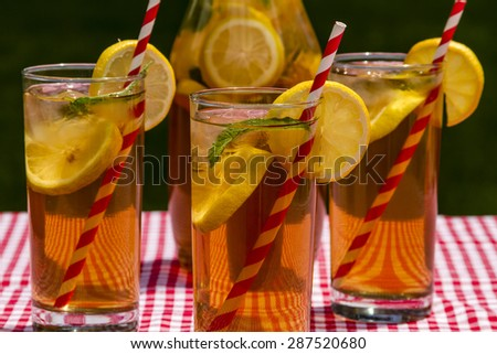 Close up of 3 tall glasses and pitcher filled with fresh brewed iced tea and lemon slices with red swirl straws sitting on a red gingham checked tablecloth on picnic table - stock photo