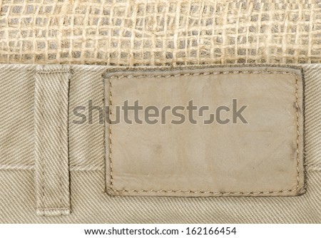 Close up of tan denim jeans with leather tag and burlap background.  Good background for Western themed business cards - stock photo
