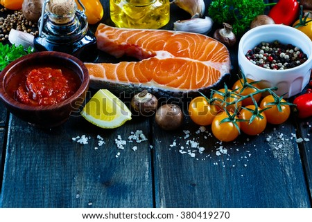 Close up of tasty fresh salmon steak with ingredients for cooking on rustic wooden background, selective focus, banner. Healthy food concept. - stock photo