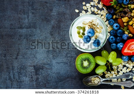 Close up of tasty ingredients (oat flakes, kiwi, berries with yogurt and seeds) for breakfast or smoothie on dark vintage background - Healthy food, Diet, Detox, Clean Eating or Vegetarian concept. - stock photo