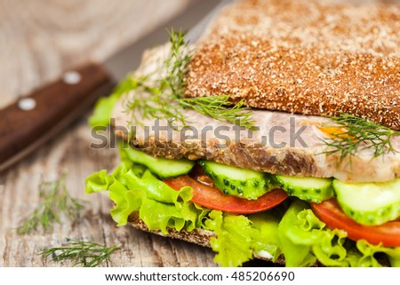 Close-up of tasty rye bread sandwiches with roast meat and vegetables, on wooden background