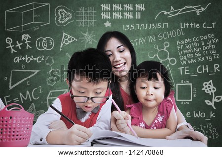Close-up of teacher and children writing in classroom - stock photo
