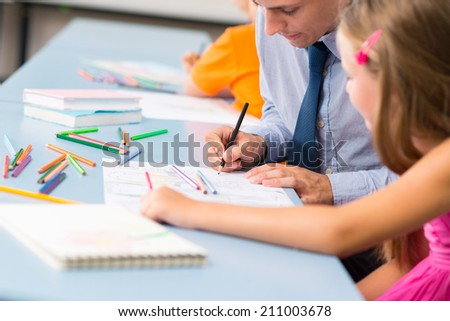 Close-up of teacher helping schoolgirl to draw a picture - stock photo