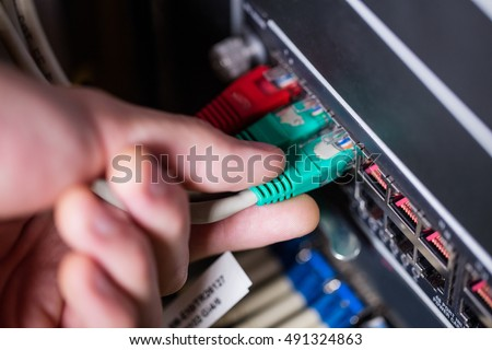 Close-Up of technician plugging ethernet in a rack mounted server in server room