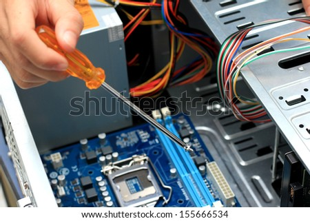 Close-up of technician's hand assembling personal computer - stock photo