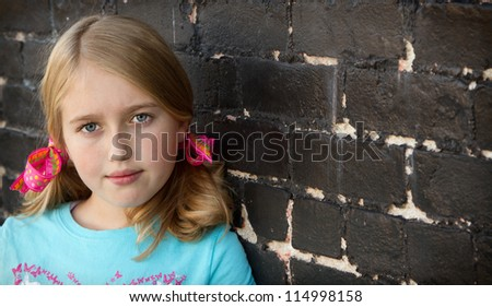 Close up of teen or child by brick wall - stock photo