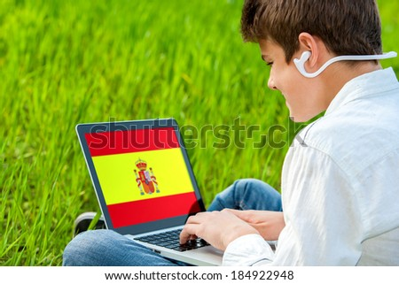 Close up of teen student taking spanish audio lessons on laptop outdoors. - stock photo