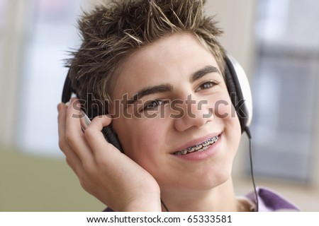 Close up of teenage boy with headset smiling - stock photo