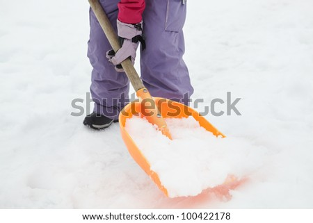 Close Up Of Teenage Girl Shovelling Snow From Path - stock photo