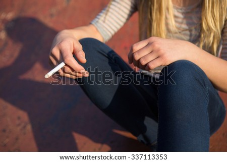 Close Up Of Teenage Girl Smoking Cigarette Outdoors