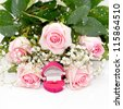 Close-up of tender pink roses with diamond ring in box on a white fabric - stock photo