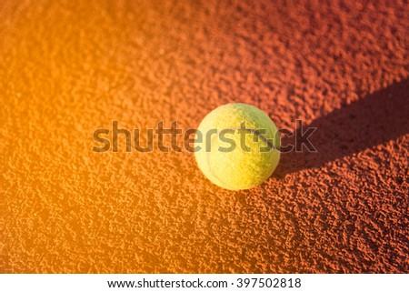 Close up of tennis ball. green color tennis ball on a tennis court sunset. - stock photo