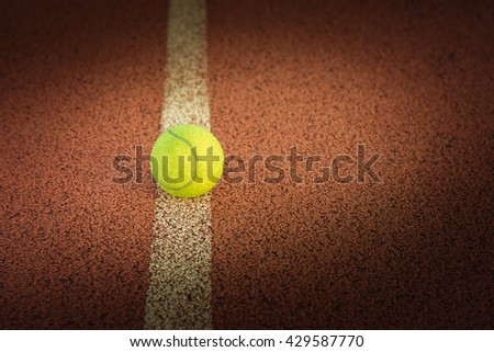Close up of tennis ball on clay court./Tennis ball ,  vintage tone - stock photo