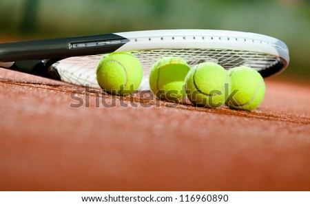 Close up of tennis racquet and balls on the clay tennis court - stock photo