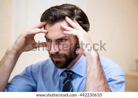 Close up of tensed man with hands on forehead at home