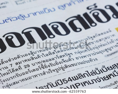 Close-up of Thai language newspaper. Shallow depth of field with some of the nearest text in focus.