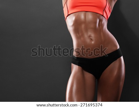 Close-up of the abdominal muscles young athlete on gray background - stock photo