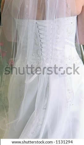 Close-up of the back of a bridal dress showing the details of the embroidery and lace.