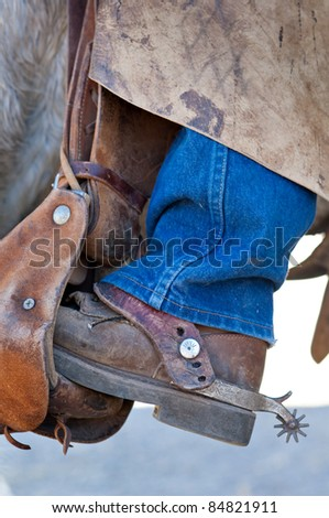 Close up of the booted foot of an old cowboy on his horse. - stock photo