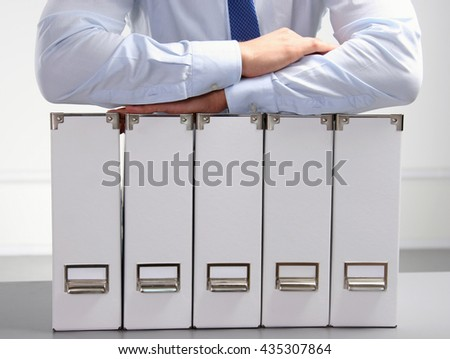 Close-up of the businessman with office folders. - stock photo