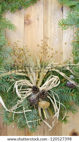 Close up of the center piece of a Christmas wreath decorated with an agricultural theme on a wooden background - stock photo