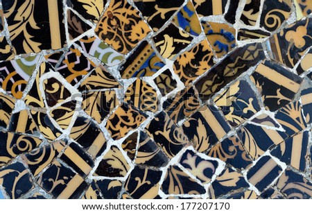 Close-up of the ceramics in Park Guell Barcelona created by Gaudi. Dark and golden. - stock photo
