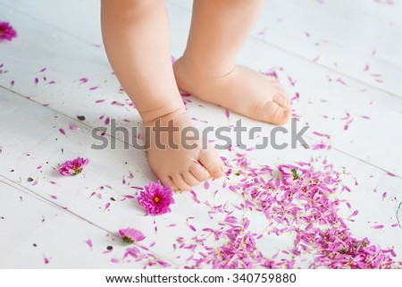 Close up of the charming small legs doing the first steps - stock photo