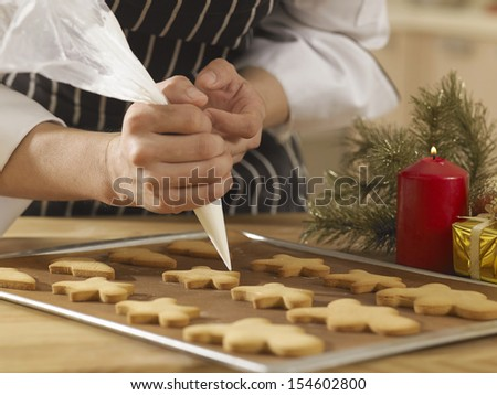 close up of the chef decorating cookies with icing sugar - stock photo