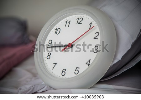 Close up of the clock on the bed as wake up in the morning concept.