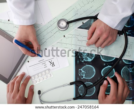 Close-up of the doctor discussions with patients in the office filled with medical data of patient - stock photo