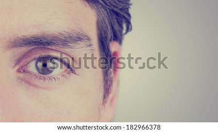 Close up of the eye and ear of a man looking straight ahead showing eyebrow, eyelash, iris, and pupil detail on a graduated grey background with copyspace. With retro filter effect. - stock photo