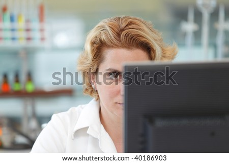 Close up of the eye of a female researcher in front of a computer monitor in a laboratory. - stock photo