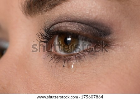 close up of the eye of a young woman with a tear drop on her lower eyelid   - stock photo
