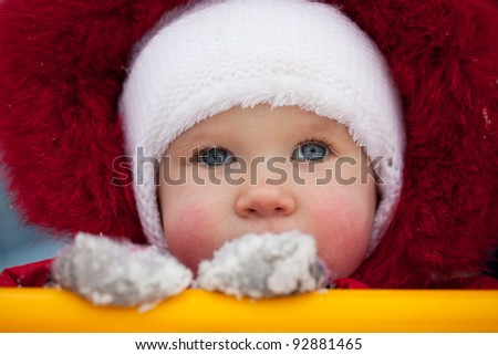 Close-up of the face a little girl in red jumpsuit - stock photo