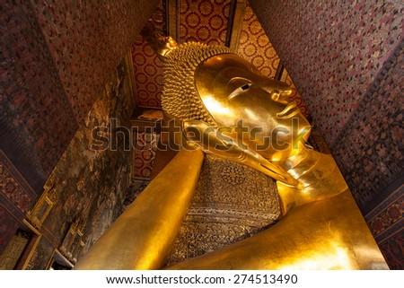 Close up of the face of Reclining Buddha in Wat Pho, Bangkok - stock photo