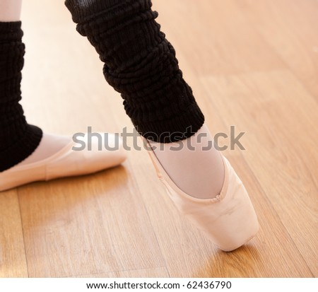 Close-up of the feet of a ballerina dancing on a wooden floor