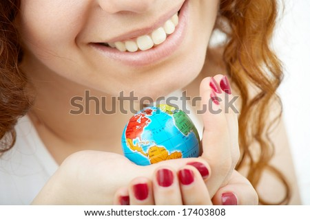 Close up of the female hands holding a copy of globe - stock photo