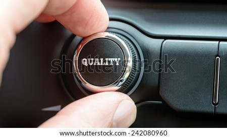 Close up of the fingers of a man turning on a Quality button with the word - Quality - in white lettering on a piece of electronic equipment. - stock photo