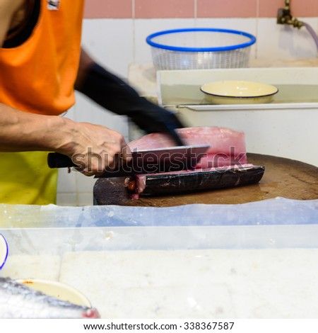 Close-up of the fishmonger�s hands cutting fish fillet with knife at Chinatown Wet Market - one of the most exotic wet markets in Singapore, situated at the iconic Chinatown Complex at Smith Street