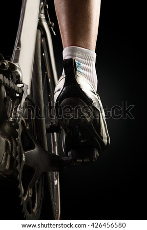 Close-up of the foot of a young man cycling. Isolated on black.