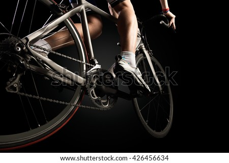 Close-up of the foot of a young man cycling. Isolated on black. - stock photo