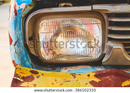 Close-up of the front headlight of an old car in garage - stock photo