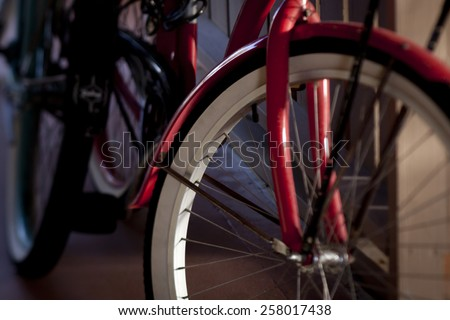close up of the front of a red bicycle with whitewall tires leaning against a carport