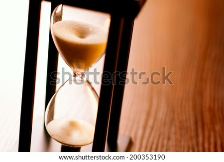 Close up of the glass bulbs on an hourglass or egg timer with running sand measuring passing time in a countdown or deadline - stock photo