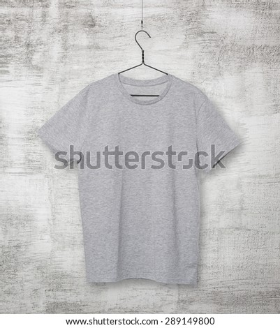 Close-up of the grey t-shirt on the clothes hanger. Concrete background. - stock photo